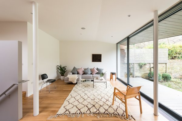 By following a set of steps, you enter into a sitting room that's part of the extension that was built towards the rear of the house. A large sliding wall of glazed glass from Fineline opens to the yard.