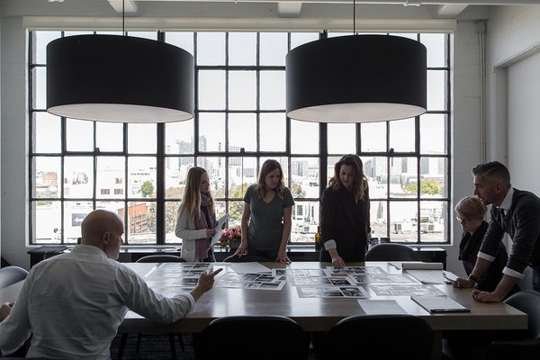In the main conference room, Hollis and a few members of her team spread out photos and plans over a custom conference table made Christian Hummler. The pendants overhead are designed by Piet Boon for Moooi.