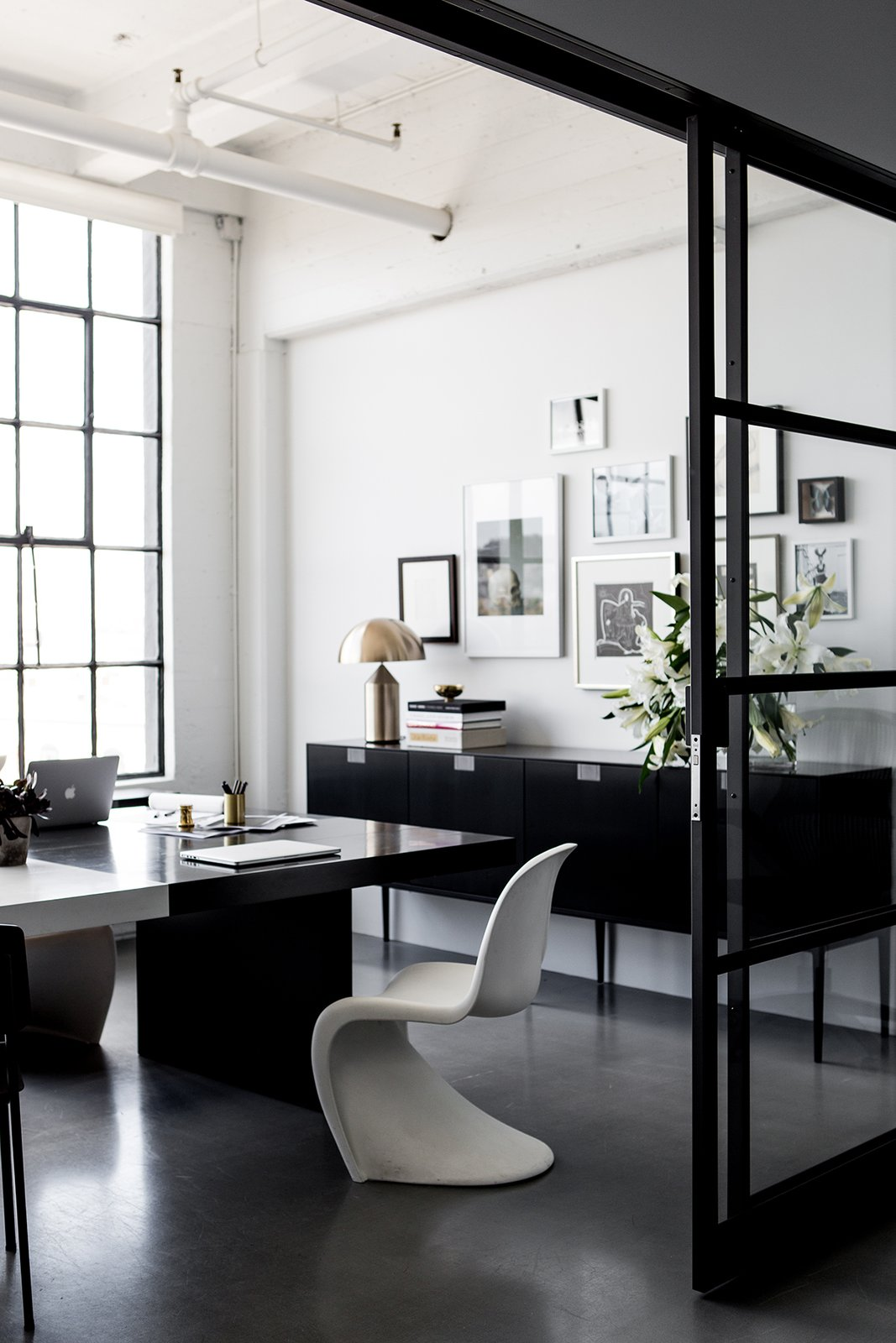 Hollis shares this office with her husband and CEO, Lewis Heathcote. Panton Chairs, designed by Verner Panton for Vitra, can be found throughout the space, which is lined with poured concrete floors throughout.  Photo 7 of 13 in A San Francisco Design Collective Reveals its Impeccably Cool Creative Studio