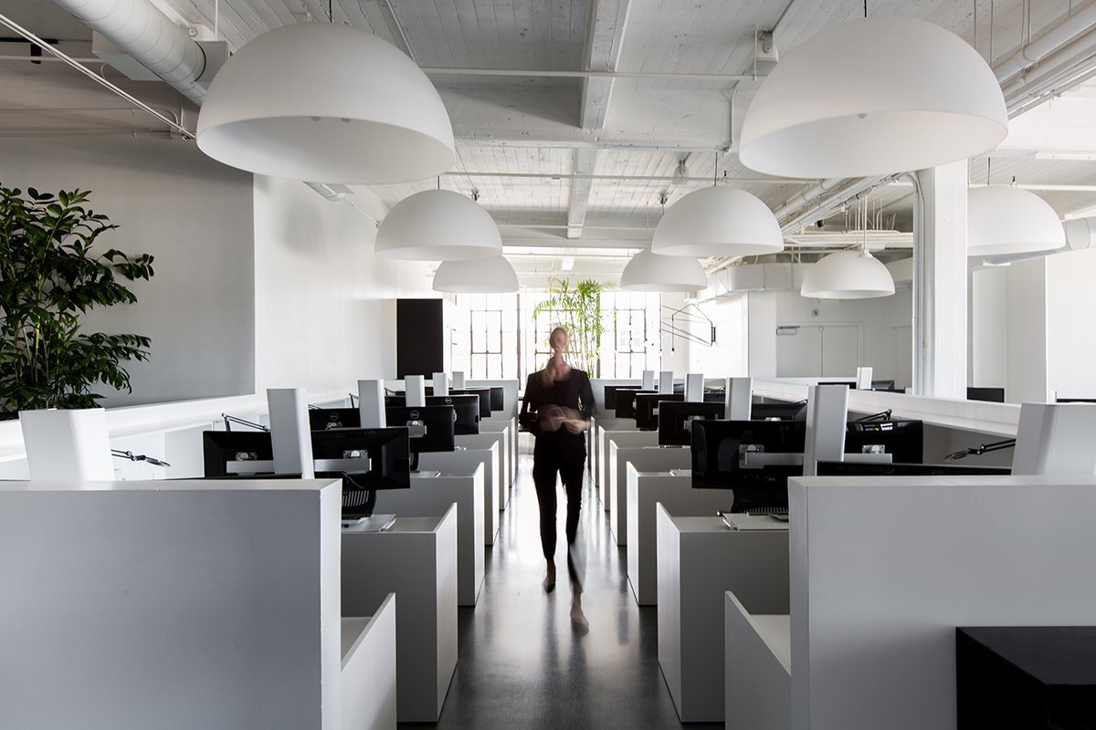 The central open work area is filled with white standing desks made by Muller Nichols and large Fontana Arte Dome pendants.