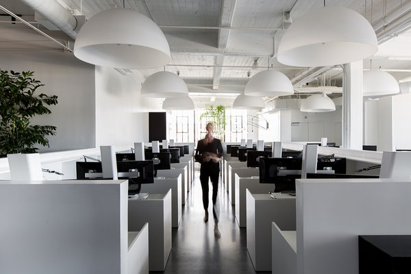 The central open work area is filled with white standing desks made by Muller Nichols, which sit under large dome pendants by FontanaArte.