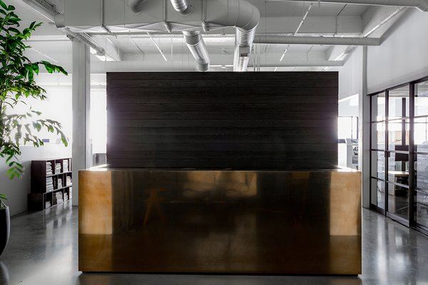 """Hollis points out, """"You move from a dark reception salon into a bright white, open space. The contrast of moving from darkness into light is always part of my work."""" The reception desk consists of a brass-clad box that was custom made by Chris French Metals, and acts as Hollis' ode to Donald Judd."""
