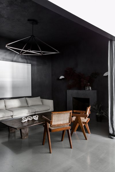 When you first enter the space, you step into a moody entry salon with hand-applied Italian integral color plaster walls and a marble fireplace. Designed to feel welcoming and residential, it's furnished with midcentury armchairs and a dramatic hanging light fixture by Bec Brittain.