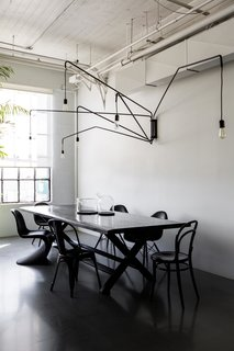 A San Francisco Design Collective Reveals its Impeccably Cool Creative Studio - Photo 7 of 12 - To create a place where employees and visitors can have family style lunches, they brought in a large dining table by James Perse. The hanging light is Lampada 046 by Dimore Studio.