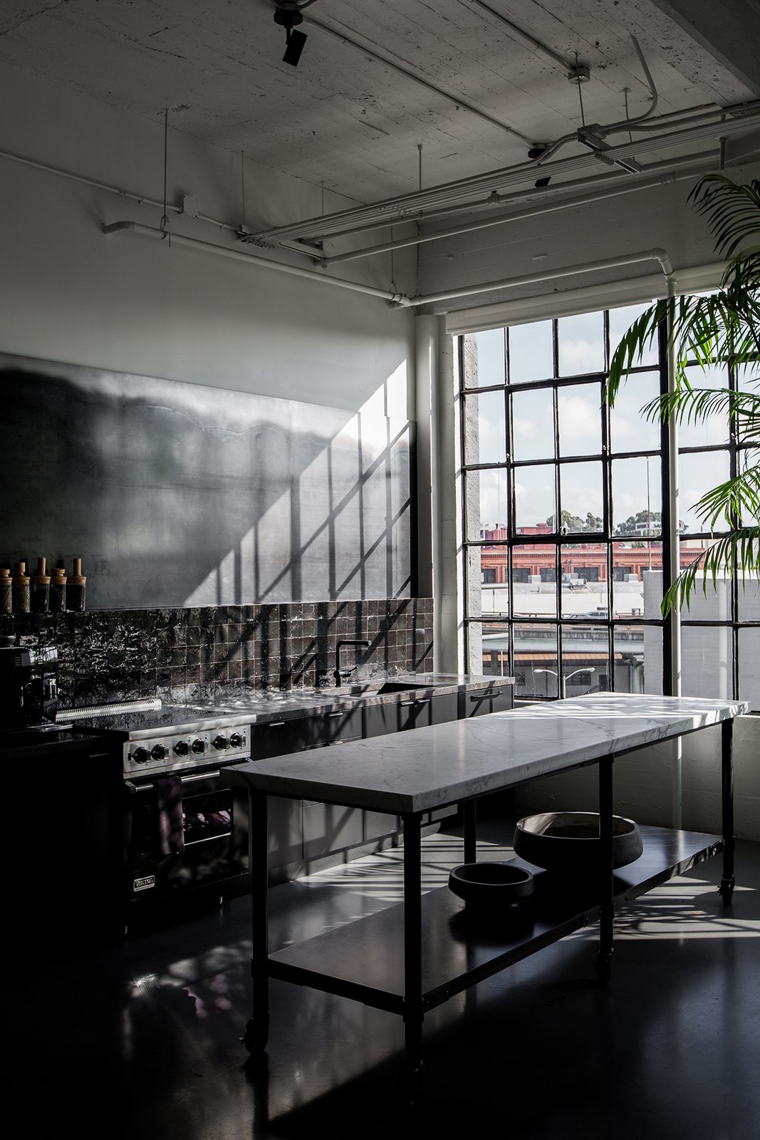 Directly next to the dining area is the dark kitchen, which has a custom island made with a metal base and a CoorItalia Calacatta marble top. Designed by Chris French, it's meant to invite socializing.  Kitchen by Jamel from A San Francisco Design Collective Reveals its Impeccably Cool Creative Studio