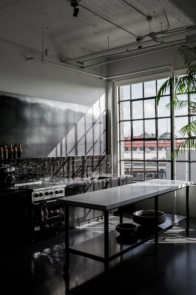 Directly next to the dining area is the dark kitchen, which has a custom island that's made with a metal base and a CoorItalia Calacatta marble top. Designed by Chris French, it's designed to invite socializing.