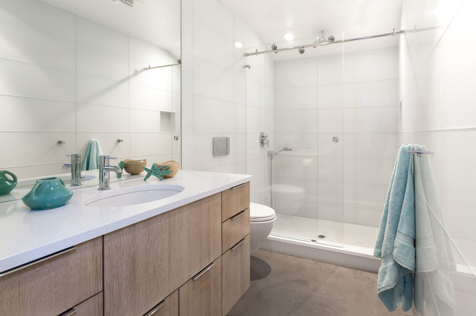 The bathroom was completely remodeled and features large glass tiles that read as one single surface material. The floors are made up of unfinished poured concrete.  Photo 7 of 10 in Bright Colors and Sleek White Oak Fill This Playful Lake Tahoe Loft