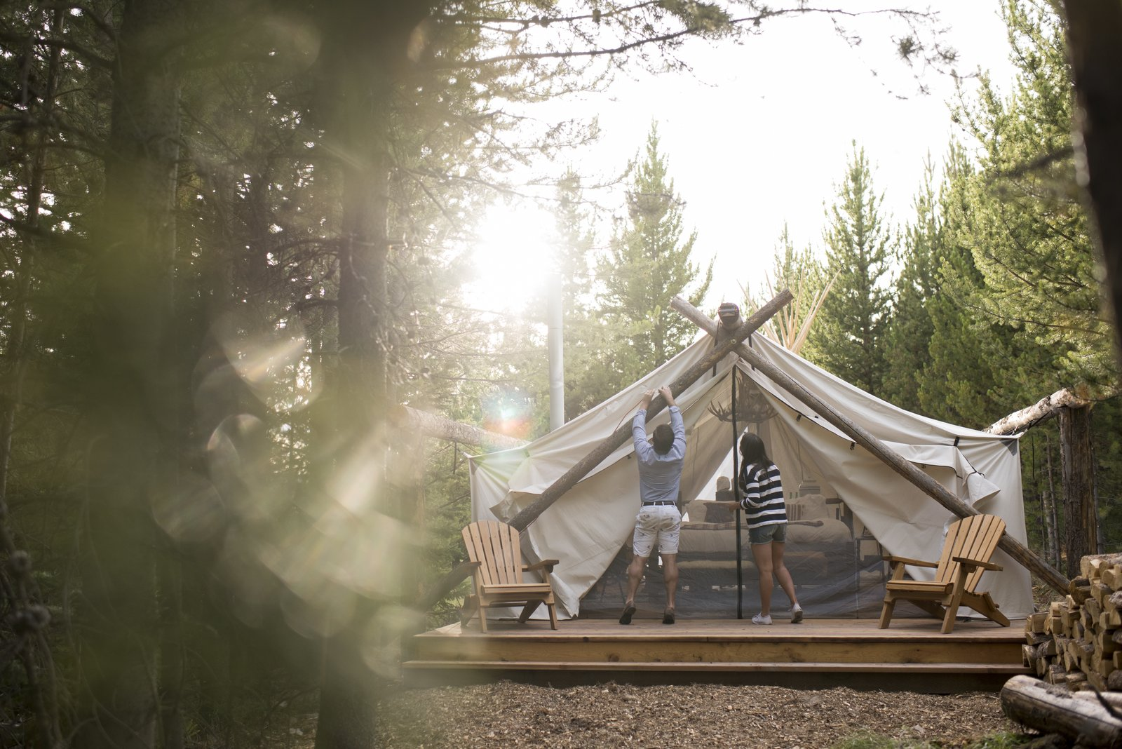 The Yellowstone location is hidden in the woods of Big Sky, Montana and is set on a freshwater pond that's surrounded by mountains. Guests have access to fly fishing and the best of both lake and forest. Tagged: Outdoor, Field, Woodland, Trees, Decking Patio, Porch, Deck, and Wood Patio, Porch, Deck.  Photo 11 of 12 in Get the Modern Camping Experience You Crave at One of These New Secluded Retreats