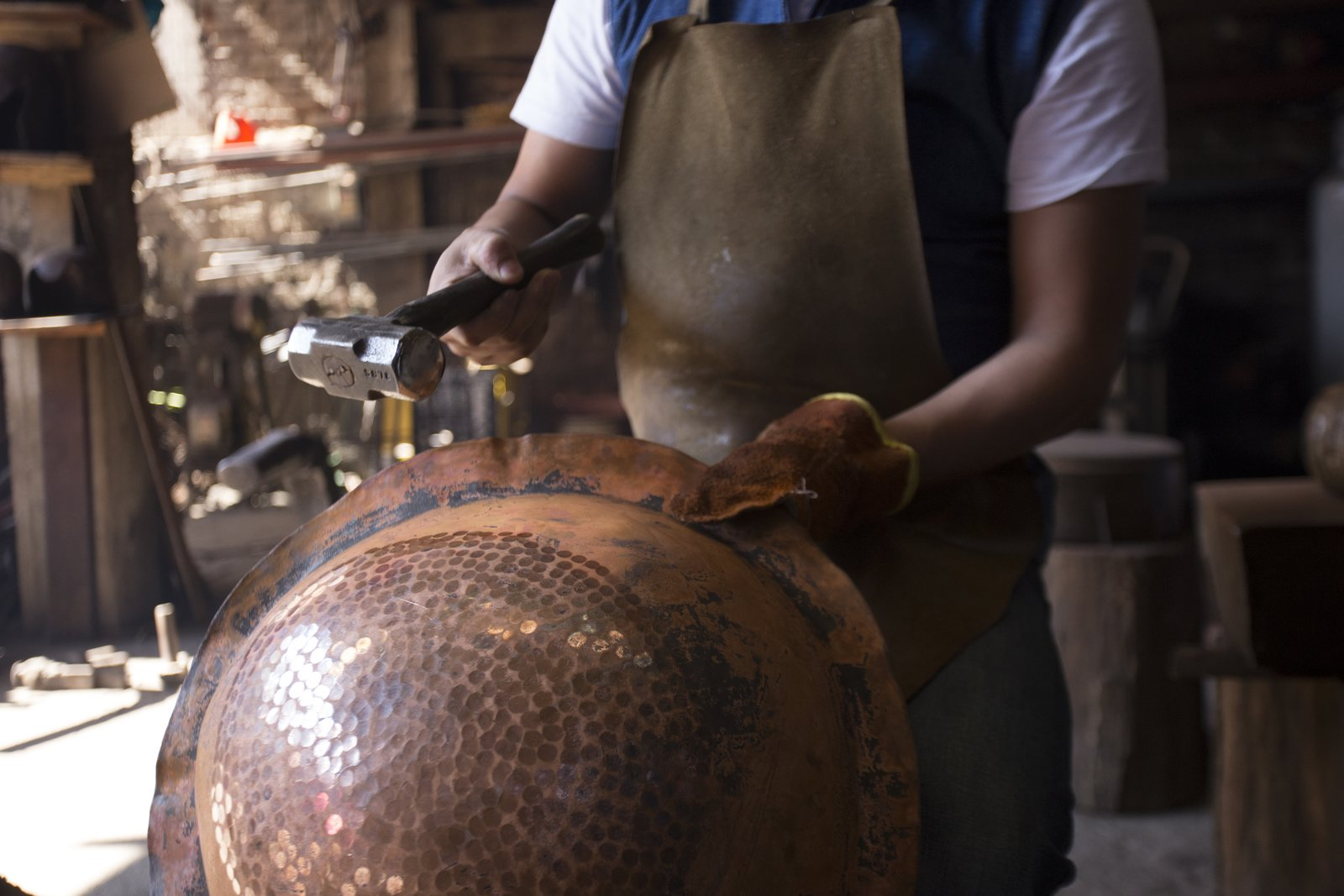 One of the traditional techniques that Filamento is fostering is working with hammered copper in Santa Clara del Cobre. For years, this skill has supported the principal commercial activity of this town, and includes knowledge that's been passed down for generations. To create these pieces, eight or  more craftsmen work together at the same time around an anvil. The copper is literally pounded when it's a state that's hot enough to be formed a certain way.