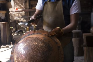 One of the traditional techniques that Filamento is fostering is working with hammered copper in Santa Clara del Cobre, Mexico. For years, this skill has supported the principal commercial activity of this town, and includes knowledge that's been passed down for generations. To create these pieces, eight or  more craftsmen work together at the same time around an anvil. Hot copper is literally pounded into its desired form.