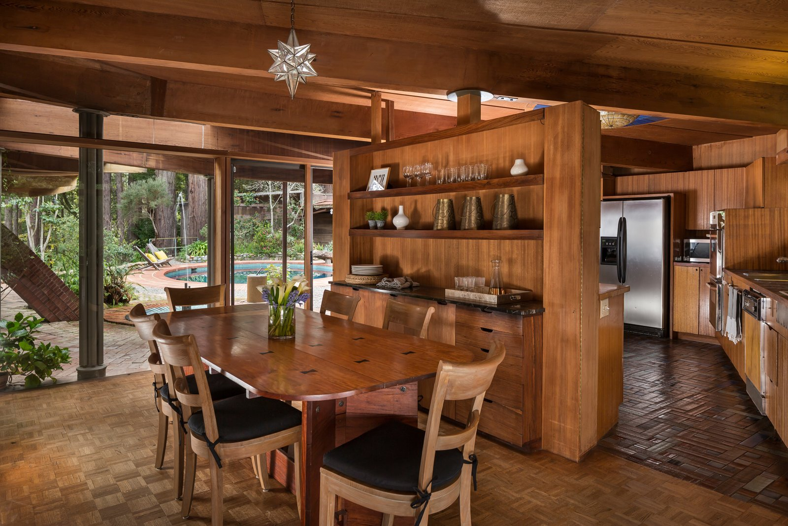 Liebermann built the dining table himself, which is clearly inspired by Frank Lloyd Wright's furniture. Little told us that the corners were so sharp to begin with, that he rounded out them out to make it work better for his large family, without losing the spirit of the table. It's made with topical hardwood and is held together with epoxy joineries.  Photo 6 of 17 in The Midcentury Home That Daniel Liebermann Built For His Parents Asks $2.8 Million