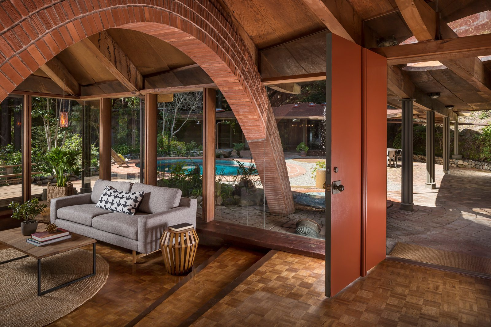 The original red front door leads directly into the living room, which has oak parquet flooring and a radiant heating system throughout that still works to this day.  Photo 3 of 17 in The Midcentury Home That Daniel Liebermann Built For His Parents Asks $2.8 Million