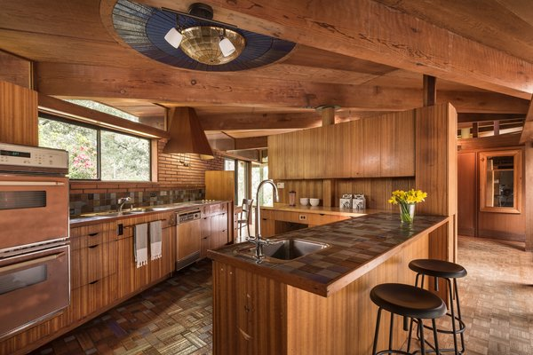 In the kitchen, the mother of pearl light fixture—which was installed by the Little family in the 1970s—is surrounded by three concentric rings of dark blue tiles from Sausalito-based Heath Ceramics. Liebermann installed Heath tiles in the kitchen, baths, pool, and fountain.