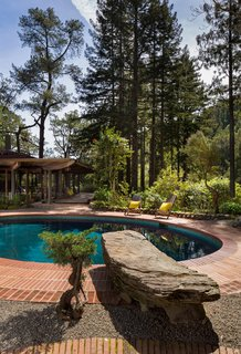 The Midcentury Home That Daniel Liebermann Built For His Parents Asks $2.8 Million - Photo 14 of 16 - A huge rock that Liebermann picked out himself acts as a diving board into the pool. Liebermann's design allows the house to reflect in the pool when you first walk in through the front gate. The reflection doubles the size of the house.