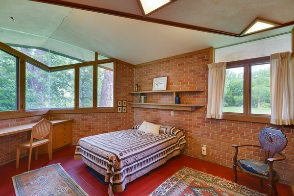 In one of the three bedrooms, Wright designed a built-in desk and graphic chair. The angular windows and skylights are continued into the bedrooms. Photo 7 of Frank Lloyd Wright's Parklands Lane modern home