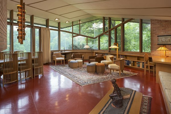 The open living space is surrounded by large, angular pieces of glass and sits on a floor made with Colorundum in a Cherokee Red, a material and color Wright often used in his work. This space also includes a brick wood-burning fireplace. Photo 3 of Frank Lloyd Wright's Parklands Lane modern home