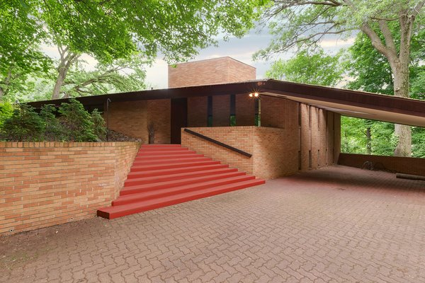Though this home is close to downtown Minneapolis, it sits on a quiet, 3.77-acre piece of land. When you approach the brick home, it immediately becomes clear that it's a Frank Lloyd Wright-designed home—thanks to its wing-like shape and Cherokee Red-painted steps. Photo 2 of Frank Lloyd Wright's Parklands Lane modern home