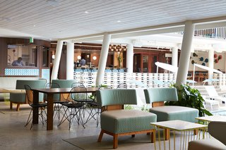 This Surf-Inspired Hotel Celebrates Waikiki's Creative Spirit and its Midcentury Roots - Photo 8 of 13 - When you make your way from reception to the elevator, this covered patio space is filled with midcentury-inspired furniture and offers fruit-infused ice water to enjoy on your way to your room. The original details of the midcentury structure are clearly highlighted in this space where many guests can be seen catching up on their emails with a complimentary coffee in-hand.