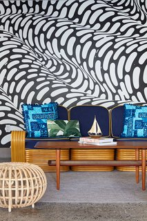 """In the covered cabana area by the pool, a hand-painted mural by Brendan """"The Blob"""" Monroe creates a funky backdrop that's inspired by the flow of water. Local artist, illustrator, and curator Jasper Wong co-curated the mural artwork dispersed throughout the property."""