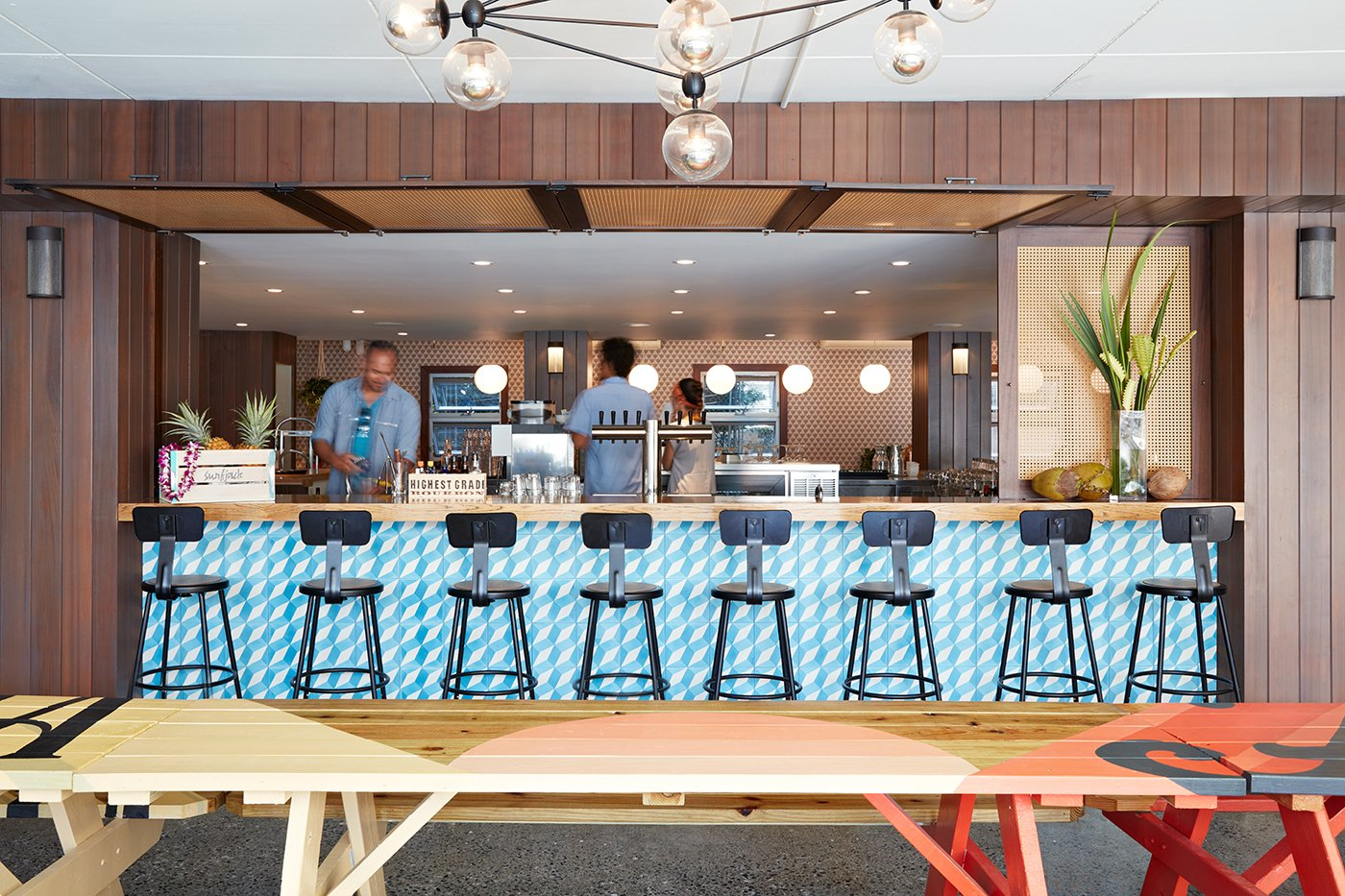 """As chef Ed Kenney's fourth eatery, Mahina & Sun's believes in, """"local first; organic whenever possible; with aloha always."""" The picnic tables next to the bar were hand-painted by local artist Jeff Gress.  Photo 6 of 14 in This Surf-Inspired Hotel Celebrates Waikiki's Creative Spirit and its Midcentury Roots"""