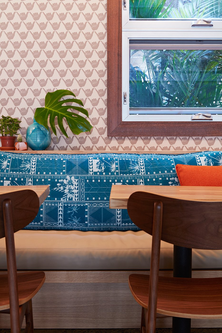 The aloha spirit runs deep in Mahina & Sun's, where the walls are covered with a shaka wallpaper by Andrew Mau. The cushions on the banquette seats were made with archived prints by Tori Richard, which were also used to create the headboards in the guest rooms and the men's uniforms. Tagged: Dining Room, Bench, Chair, and Table.  Photo 7 of 14 in This Surf-Inspired Hotel Celebrates Waikiki's Creative Spirit and its Midcentury Roots