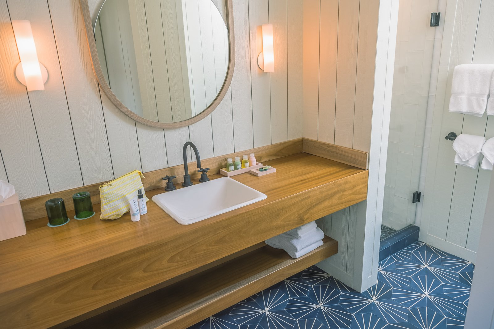 The bathrooms are filled with North Shore toiletries and custom ceramic floor tiles. Andrew Mau, who designed the shaka wallpaper in the restaurant, also created the Moana Vanity Mirrors.