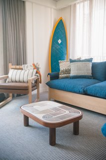 Studio Collective designed the 112 rooms and took inspiration from the bungalows that can be found on Oahu's North Shore. They feature reed ceilings, batten walls, local art, and bespoke coffee tables that are topped with ceramic tiles.