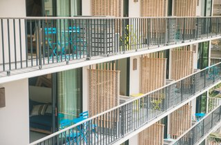 This Surf-Inspired Hotel Celebrates Waikiki's Creative Spirit and its Midcentury Roots - Photo 13 of 13 - On each of the 10 floors, the balcony rooms have private lanais that are divided by woven screens for privacy. While sitting on the brightly-hued outdoor chairs, you'll look out to other midcentury buildings while planning your tropical adventure ahead.
