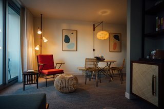 The rooms also include custom lounge chairs, tables, spring pole lamps, and rattan chairs.