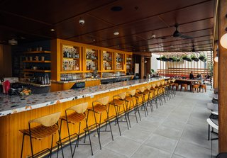 """The bar is lined with vintage stools by Arthur Umanoff, which OMFGCO sourced from all over the world via 1stdibs, Pamono, Etsy, and more. Fritz Mesenbrink of OMFGCO tells us, """"It was challenging to get that many of his stools in the same place, but we got them, and had them all restored beautifully."""""""