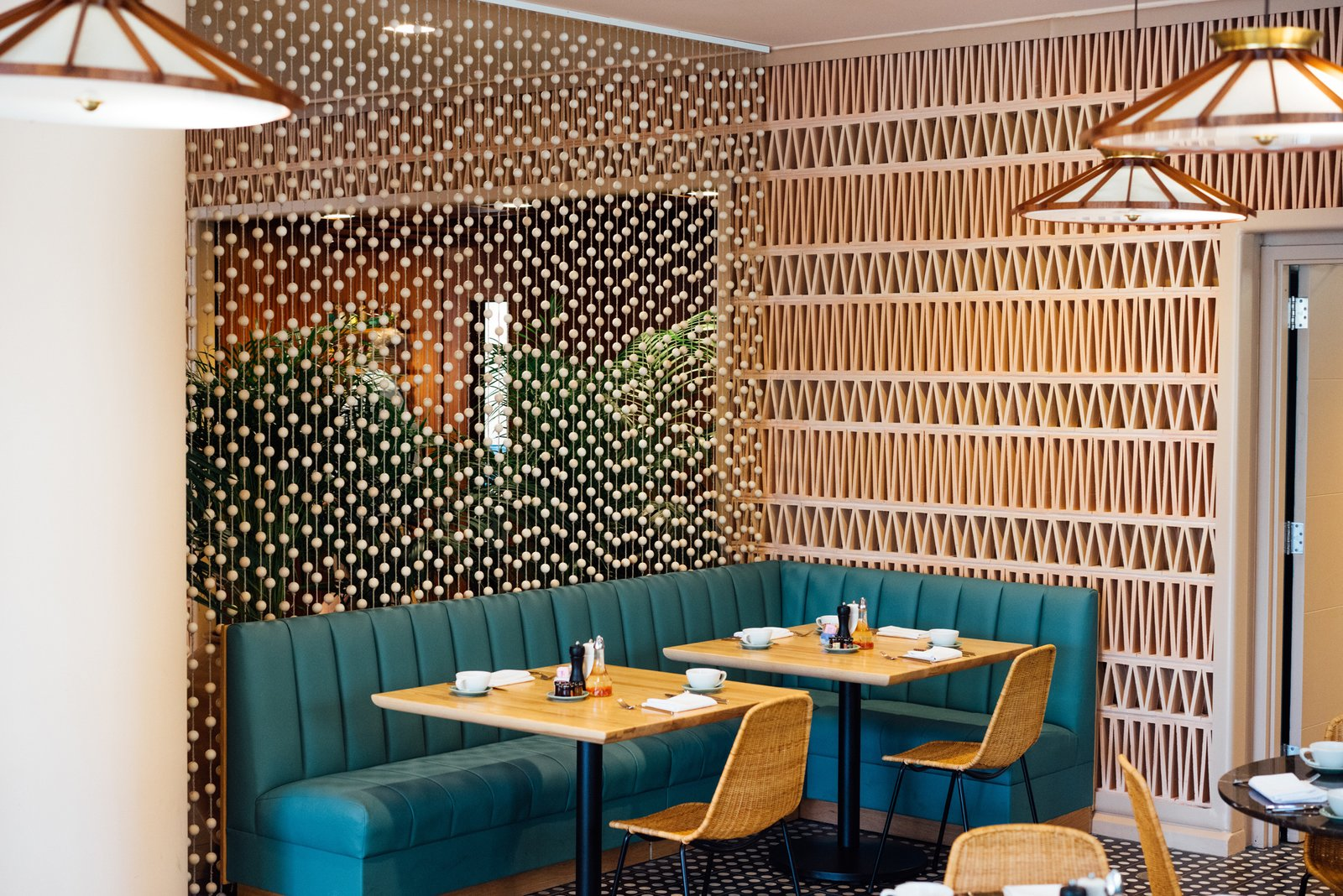 Along with creative craft cocktails coming from the bar, the on-site restaurant serves Pacific Rim and American comfort food. Jewelry designer Anne Korte of AK Studio made the custom curtain for the project. Waikiki's Midcentury Revival Continues to Flourish With a New Jet Set-Inspired Hotel - Photo 14 of 18