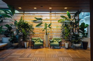 A 100-foot-long wall of terra-cotta breeze blocks designed by Patricia Urquiola for Mutina surrounds the reception desk and extends into a seating area.