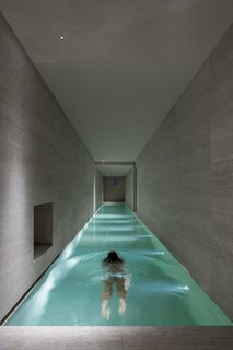 10 Exquisitely Modern Homes in Italy - Photo 6 of 10 - And even in areas where the light is a more pragmatic tool, it is integrated wonderfully, as in the long indoor pool and in the minimally modern bathroom. Each light feels like an architecture in and of itself, dancing through the home in a game of reflection and feedback. So while the home stands proudly during the day, it is at night that its true nature comes to light.