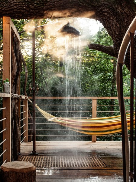 Outside, on the wooden deck, a hammock invites guests to take a break and unwind; an open-air tree shower offers the perfect opportunity to freshen up after exploring the forest, just before enjoying a meal prepared on the barbecue or a pizza baked in the wood fired pizza oven. A spiral staircase leads to the top level where a hot tub and a sauna provide the ultimate relaxation experience among ancient oak trees.