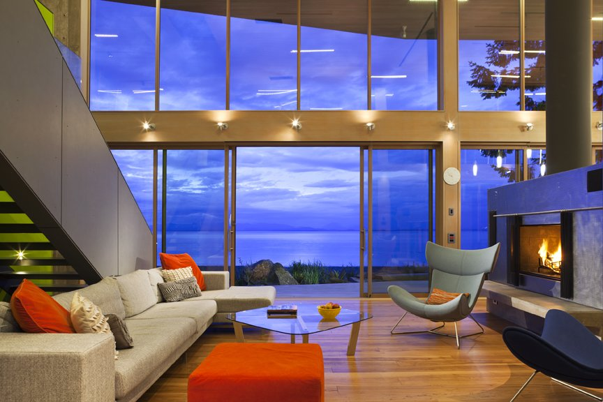 The broad interior two-story living room is a thickened wooden frame to view the Georgia Straight beyond, where wild winter storms rage and bald eagles hunt.   #livingroom #bright #hearth #beachhouse #beachhouses #evening #oceanfront #oceanviews #britishcolumbia #vancouverislands #comox #interstice #intersticearchitects #interiordesign #bradlaughton #bradlaughtonphotography  TreeHugger by INTERSTICE Architects