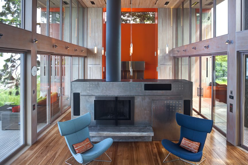 Corrugated-steel room divider / hearth with a fireplace inside.   #interstice #intersticearchitects #hearth #roomdivider  #bradlaughton #bradlaughtonphotography #orange #bright #color #kitchen #livingroom #diningroom #cabinetry  #highceilings #beachhouses #beachhouse  #britishcolumbia #vancouverisland #smokestack  TreeHugger by INTERSTICE Architects