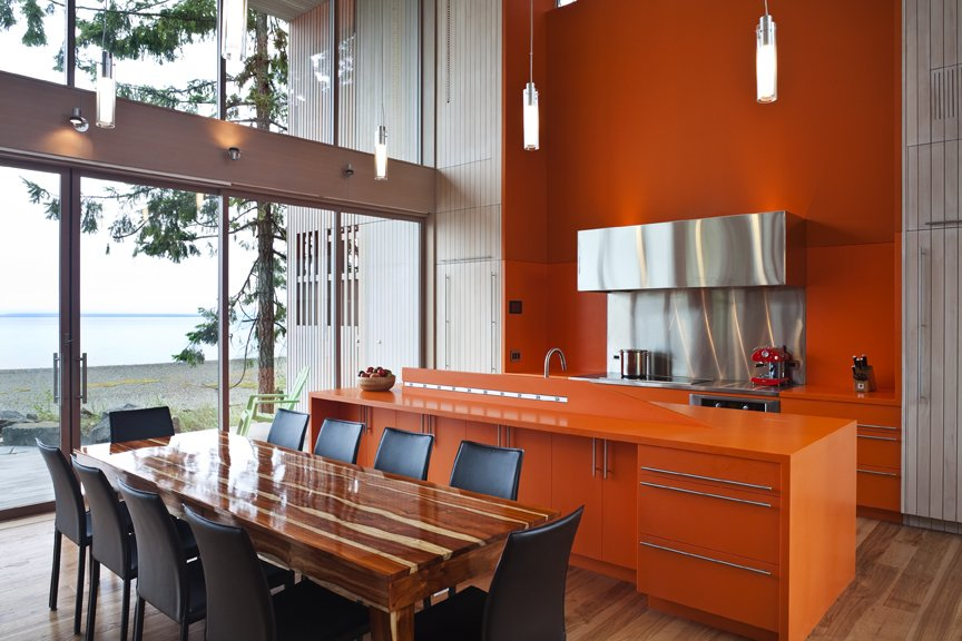 Woven through the raw palette of glass, concrete, wood, and Corten steel are two strong color gestures, including this bright orange paint and corian countertops and cabinetry.    #kitchen #corian #custom #waterfront #oceanfront #view #diningroom #orange #bright #color #beachhouse #beachhouses #vancouverisland #britishcolumbia #view #interstice #intersticearchitects #bradlaughtonphotography #bradlaughton