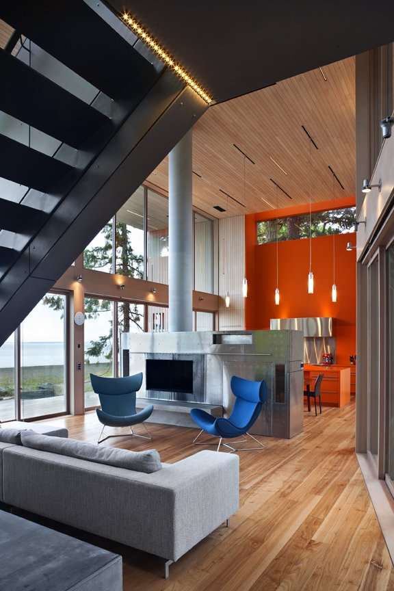 A bold orange vertical excavation of the frame accents the kitchen and provides a second bright counterpoint to the long, grey, Canadian winters.   #kitchen #bright #color #orange #hearth #livingroom #beachhouse #oceanfront #beachhouses #britishcolumbia #vancouverisland #interstice #intersticearchitects #bradlaughton #bradlaughtonphotography