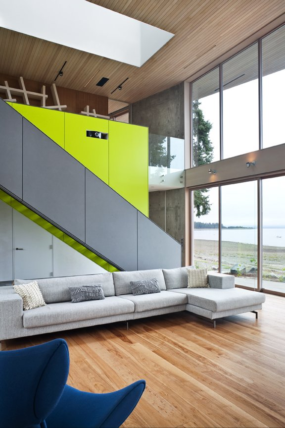 A sleek  staircase leads from the living room to a study. The bright green accent wall includes storage for a projector and book case.   #green #limegreen #bright #color #livingroom #entertainmentroom #staircase #storage #beachhouse #beachouses #interstice #intersticearchitects #bradlaughton #bradlaughtonphotography #britishcolumbia #vancouverisland  TreeHugger by INTERSTICE Architects