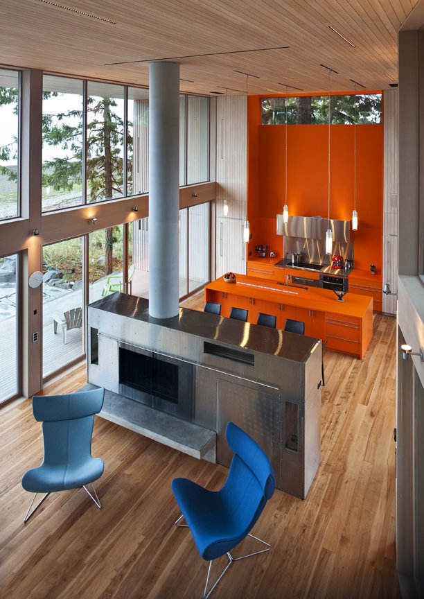 The kitchen and dining area is an open space which is filled with bright, warm  color, in this case an island and cabinets in orange Corian.  #orange #bright #color #kitchen #livingroom #diningroom #cabinetry #corian #hearth #highceilings #beachhouses #beachhouse #interstice #intersticearchitects #bradlaughton #bradlaughtonphotography #britishcolumbia #vancouverisland