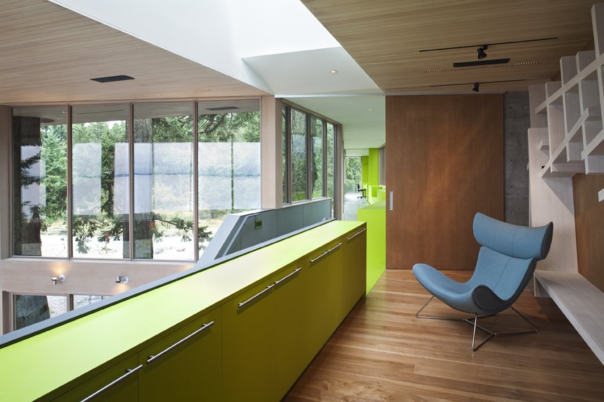 This strong color gesture of green traces the entry path from the guest house to the main house, providing cabinetry along the glass walk way. The door to the walkway, which is opened in this photo, slides closed to divide off the two volumes.   #green #limegreen #bright #color #walkway #hallway #staircase #storage #beachhouse #beachouses #interstice #intersticearchitects #bradlaughton #bradlaughtonphotography #britishcolumbia #vancouverisland