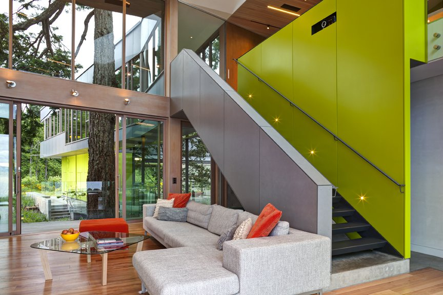 A sleek  staircase leads from the living room to a study. The bright green accent wall includes storage.   #green #limegreen #bright #color #livingroom #entertainmentroom #staircase #storage #beachhouse #beachouses #interstice #intersticearchitects #bradlaughton #bradlaughtonphotography #britishcolumbia #vancouverisland TreeHugger by INTERSTICE Architects