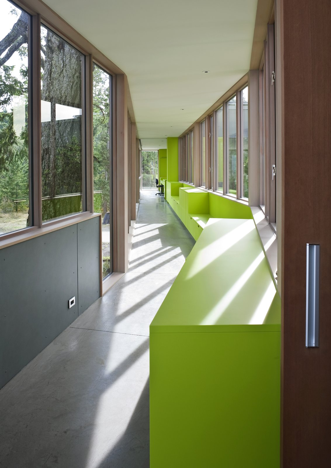 The semi-enclosed glass bridge walkway extends through the trees from the seasonally closable Guest house . The bright green color follows into the walkway, and covers the custom cabinetry and seating along the bridge.   #bridge #walkway #green #limegreen #glass #residential #hallway #beachhouse #beachhouses #bright #color #interstice #intersticearchitects #britishcolumbia #vancouverisland #bradlaughton #bradlaughtonphotography