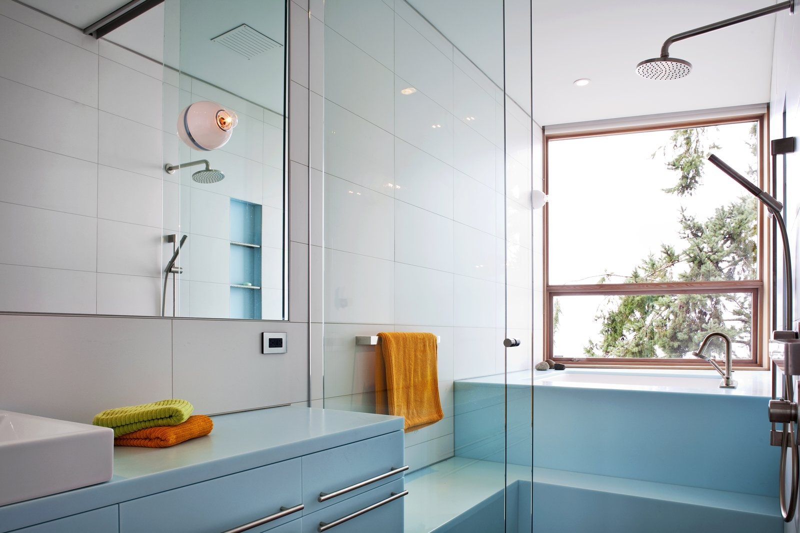 The pale blue of this bathroom in the main house creates a peaceful, serene atmosphere. The seating shower stalls, and a tub that provides a view to the outdoors makes for an incredibly luxurious, rejuvenating experience.   #paleblue #bathroom #shower #bath #tub #color #bright #beachhouse #glass #showerdoor #minimal #modern #relaxing #spa #interstice #intersticearchitects #interiorarchitecture #bathroomdesign #bradlaughton #bradlaughtonphotography   TreeHugger by INTERSTICE Architects