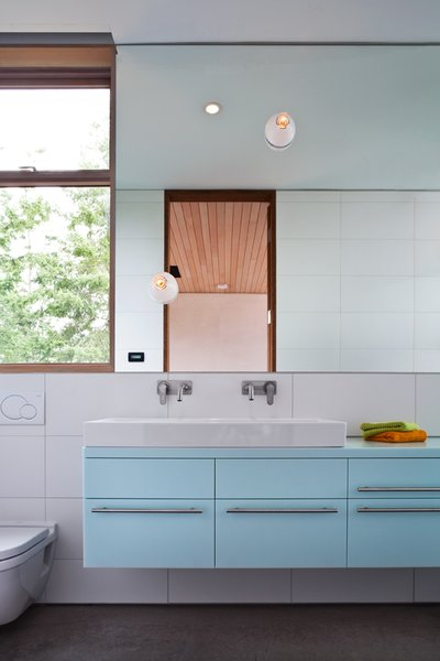 The pale blue of this bathroom in the main house creates a peaceful, serene atmosphere.  #paleblue #bathroom  #color #bright #beachhouse #minimal #modern #relaxing  #interstice #intersticearchitects #interiorarchitecture #bathroomdesign #bradlaughton #bradlaughtonphotography Photo 20 of TreeHugger modern home