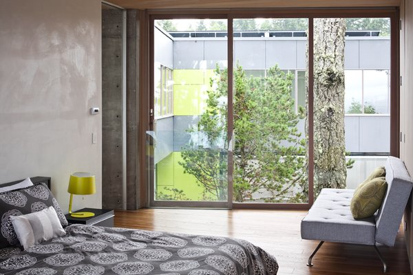 The minimal bedroom reflects the raw material palette of glass, concrete, wood, and Corten steel. This bedroom has a view to the separate volume, and to a large Douglas fir between the two  spaces.   #bedroom #nature #residential #interstice #intersticearchitects #bradlaughton #bradlaughtonphotography Photo 19 of TreeHugger modern home