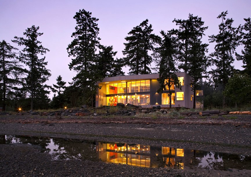 """View from the beach at low tide. The house dwells lightly on the beachfront, providing the unique spatial intimacy of being in and among the trees and in between the wild ocean and the soft wetlands. The projects creates an incomplete """"room without walls"""" from which to enjoy the pristine landscape in an atmosphere of stewardship and ecological sensitivity.   #residential #residentialarchitecture #beachhouse #beachhouses #interstice #intersticearchitecture #evening #view #nature #outdoors #britishcolumbia #comox #vancouverislands #bradlaughton #bradlaughtonphotography #facade   TreeHugger by INTERSTICE Architects"""