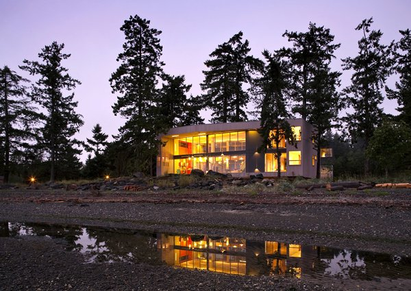 """View from the beach at low tide. The house dwells lightly on the beachfront, providing the unique spatial intimacy of being in and among the trees and in between the wild ocean and the soft wetlands. The projects creates an incomplete """"room without walls"""" from which to enjoy the pristine landscape in an atmosphere of stewardship and ecological sensitivity.   #residential #residentialarchitecture #beachhouse #beachhouses #interstice #intersticearchitecture #evening #view #nature #outdoors #britishcolumbia #comox #vancouverislands #bradlaughton #bradlaughtonphotography #facade  Photo 11 of TreeHugger modern home"""