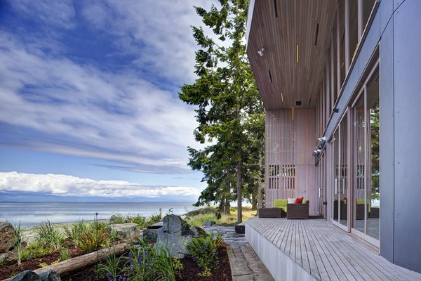 The main house is clad in the local Douglas fir with deep protective eaves, stained grey to match the sun-bleached drift wood logs that litter the coast.   #facade #residential #residentialarchitecture #coastline #beachhouse #beachhouses #view #porch #beachfront #britishcolumbia #vancouverislands #bradlaughton #bradlaughtonphotography  Photo 10 of TreeHugger modern home