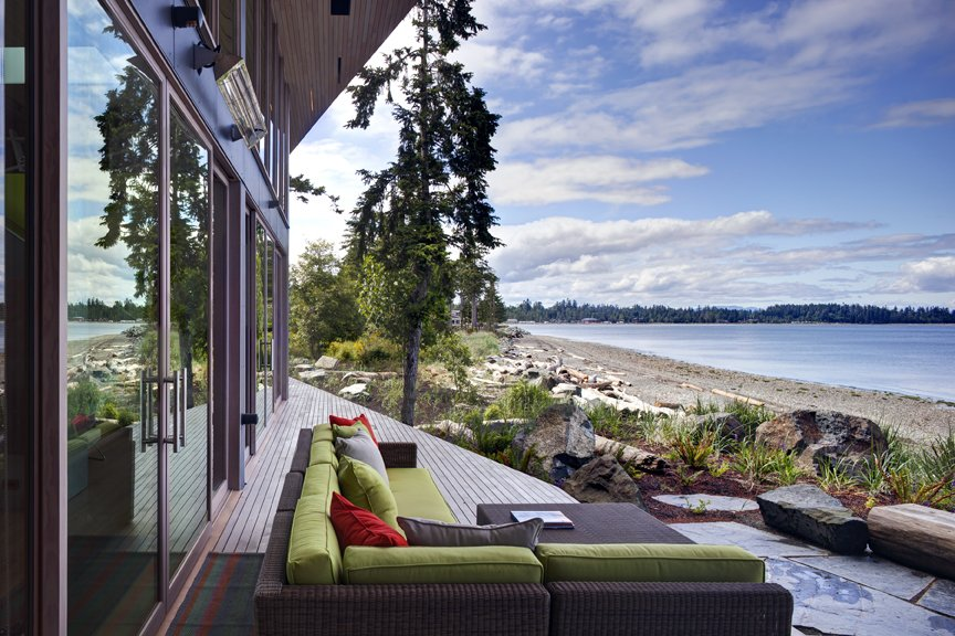 The main house is clad in the local Douglas fir with deep protective eaves, stained grey to match the sun-bleached drift wood logs that litter the coast. #facade #residential #residentialarchitecture #coastline #beachhouse #beachhouses #view #porch #beachfront #britishcolumbia #vancouverislands #bradlaughton #bradlaughtonphotography